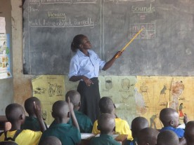 Akello Catherine teaching phonics to P1 at Layibi Techo Primary.