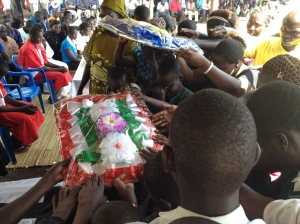 Children and parents offer flowers at the burial of Teacher Dorine this week.