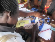 A nursery teacher practising letter formation skills led by Teach Caroline.
