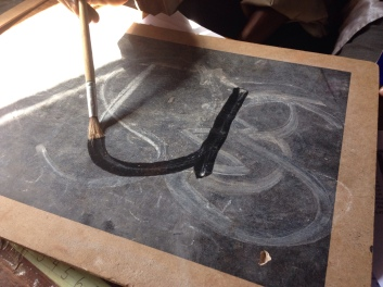 Tracing the outline of a letter with a paintbrush and water